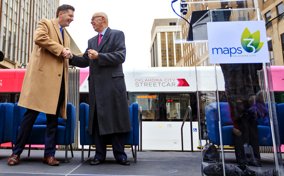 Photo - Mayor David Holt and Tom McDaniel, from left, shake hands as they arrive  outside of Leadership Square to celebrate the grand opening ceremony of the Oklahoma City streetcar system in downtown Oklahoma City, Okla. on Friday, Dec. 14, 2018. Photo by Chris Landsberger, The Oklahoman
