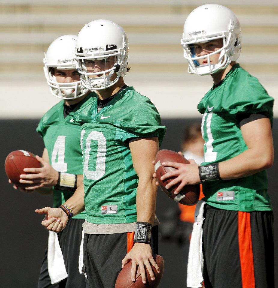 Photo - From left, quarterbacks J.W. Walsh (4), Clint Chelf (10) and Wes Lunt (11) wait for the start of a drill during OSU spring football practice at Boone Pickens Stadium on the campus of Oklahoma State University in Stillwater, Okla., Monday, March 12, 2012. Photo by Nate Billings, The Oklahoman