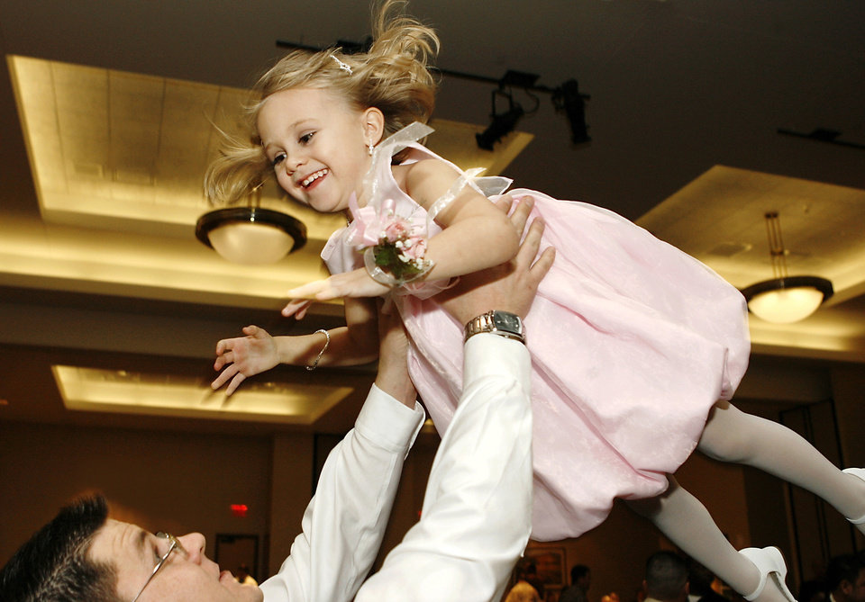 Photo - Travis Worth, tosses his 4-year-old daughter, Lailynn, above his head much to her delight as the pair danced during the final session of  the Daddy-Daughter Dance at the Reed Center in Midwest City Saturday night, Feb. 7, 2009. The annual event is hosted by the Midwest City Parks and Recreation Department.   BY JIM BECKEL, THE OKLAHOMAN