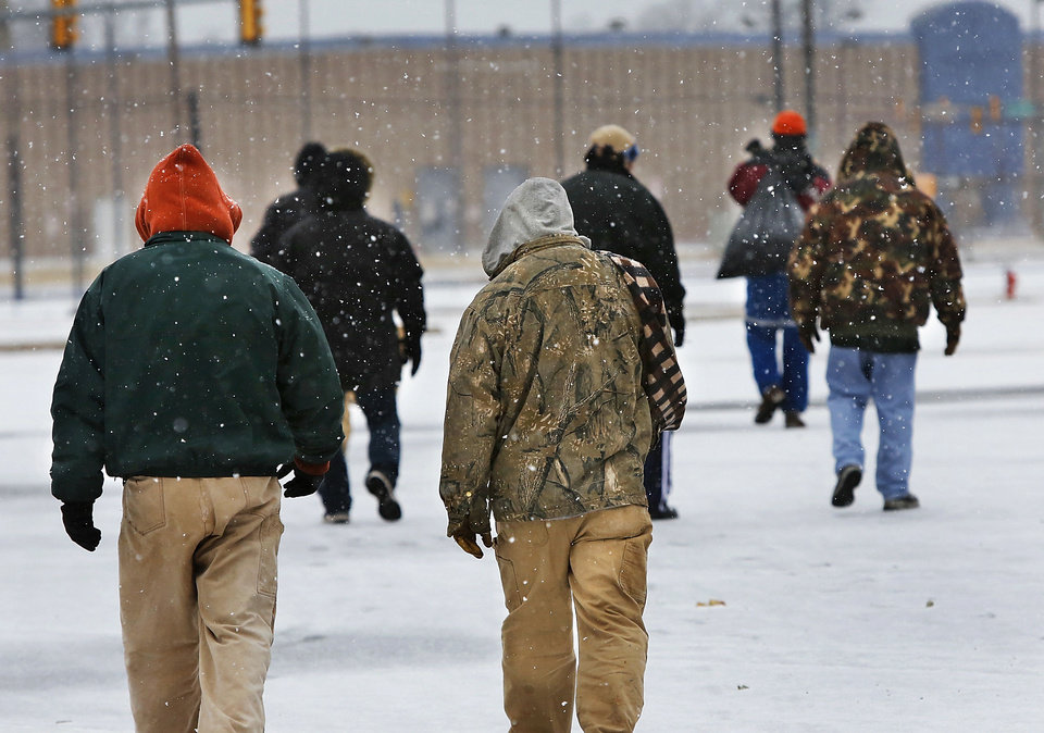 Men walk across a snow-covered lot Tuesday after leaving the Red Andrews Christmas Dinner in downtown Oklahoma City. Photo by Jim Beckel, The Oklahoman