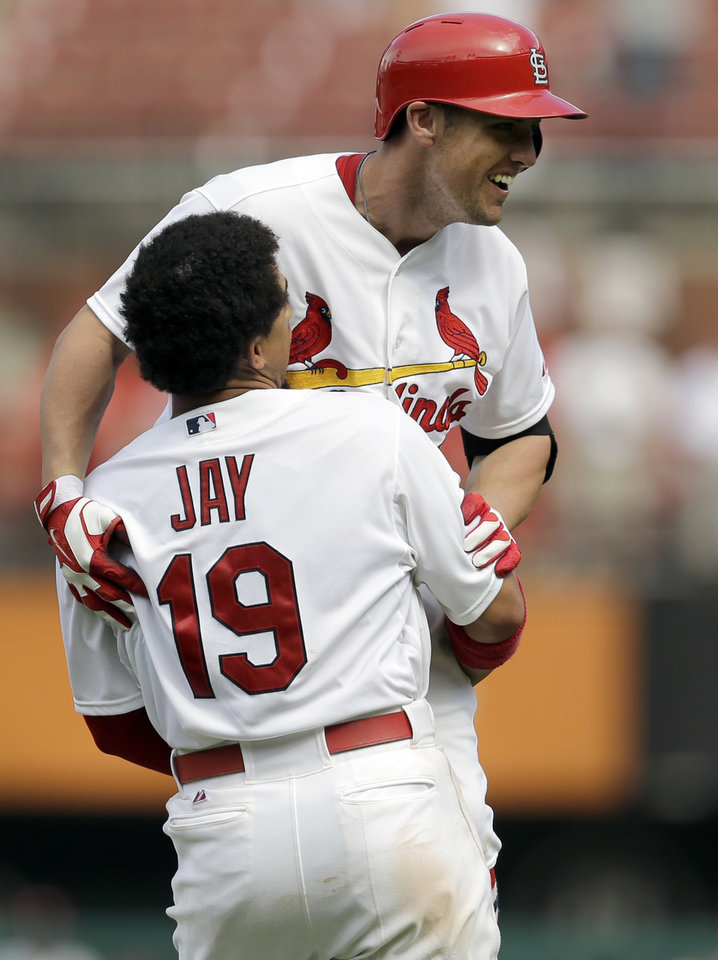 Photo - St. Louis Cardinals' Peter Bourjos, top, is congratulated by teammate Jon Jay (19) after hitting a walkoff-single to score Yadier Molina during the ninth inning of a baseball game against the Pittsburgh Pirates, Wednesday, Sept. 3, 2014, in St. Louis. The Cardinals won 1-0. (AP Photo/Jeff Roberson)