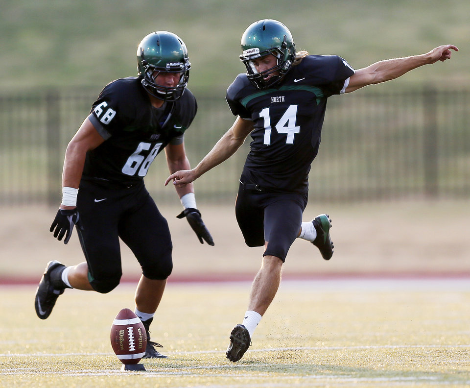 Norman North's Redford Jones (14) kicks off next to teammate Evan Coles (68) during a high school football scrimmage at Moore Stadium between Edmond Santa Fe and Norman North in Moore, Okla., Thursday, Aug. 16, 2012. Photo by Nate Billings, The Oklahoman