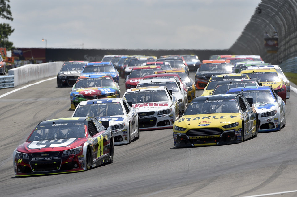 Photo - Jeff Gordon (24) leads Marcos Ambrose (9) and Jimmie Johnson (48) on a restart during a NASCAR Sprint Cup Series auto race at Watkins Glen International, Sunday, Aug. 10, 2014, in Watkins Glen N.Y. (AP Photo/Derik Hamilton)