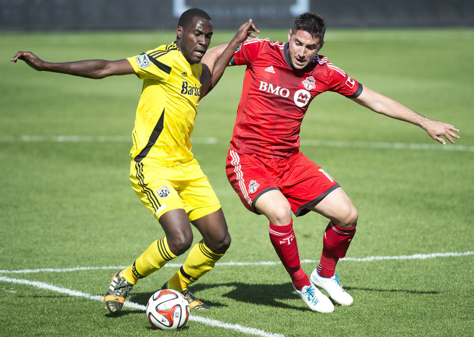 Photo - Toronto FC midefielder Brad Orr, right, competes for the ball against Columbus Crew midfielder Tony Tchani during the first half of an MLS soccer game in Toronto on Saturday, May 31, 2014. (AP Photo/The Canadian Press, Nathan Denette)