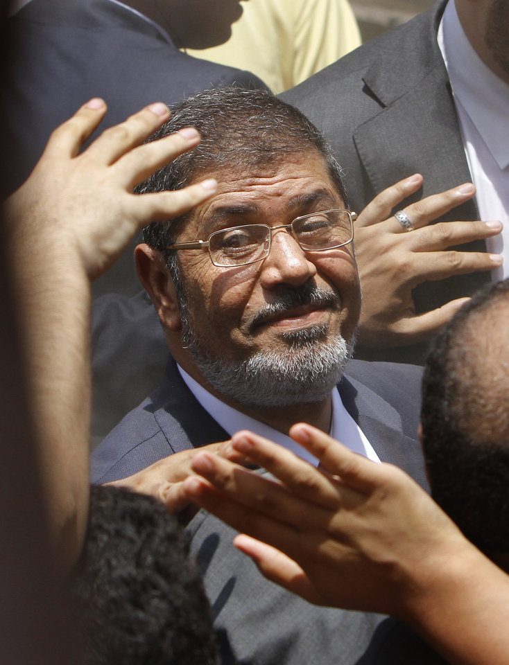 Photo -   FILE - In this Saturday, June 16, 2012 file photo, supporters wave to Egyptian presidential candidate Mohammed Morsi after he cast his vote at a polling station in Zagazig, 63 miles (100 kilometers) northeast of Cairo, Egypt. (AP Photo/Amr Nabil, File)
