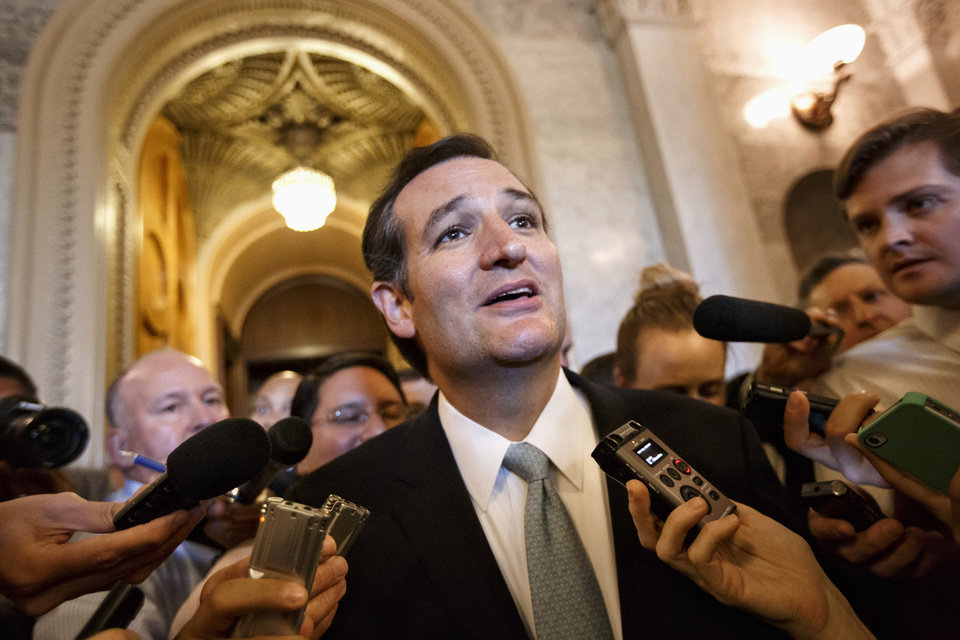 Photo - Sen. Ted Cruz, R-Texas, talks to reporters as he emerges Wednesday from the Senate Chamber on Capitol Hill in Washington, after his overnight crusade railing against the Affordable Care Act, popularly known as