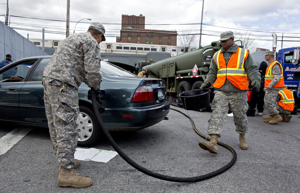 Photo -   New York National Guard personnel pump gas into a vehicle as up to ten gallons of free gas is given away in the Jamaica neighborhood of the Queens borough of New York, Saturday, Nov. 3, 2012, in the wake of Superstorm Sandy. Trucks are being provided by the U.S. Department of Defense at the direction of President Barack Obama and are being deployed in coordination with the New York National Guard at the direction of the governor. (AP Photo/Craig Ruttle)