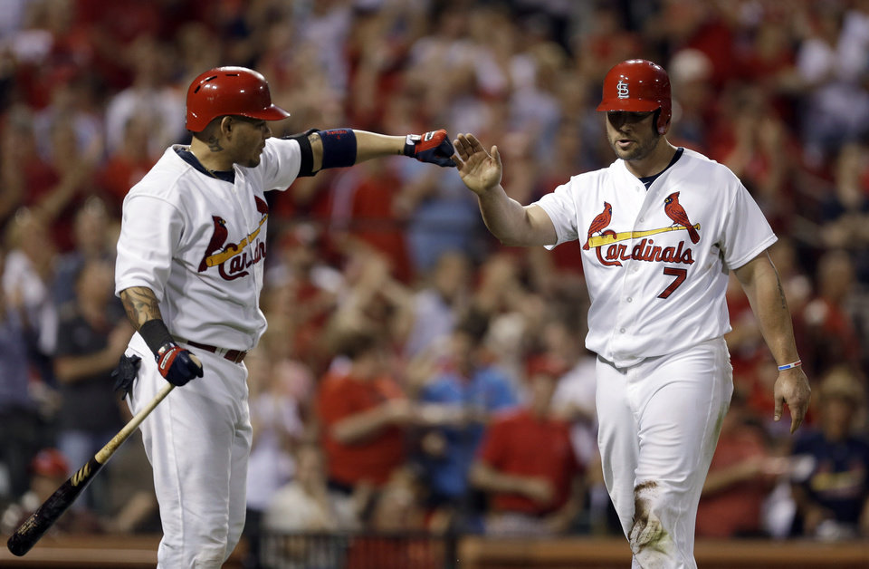 Photo - St. Louis Cardinals' Matt Holliday, right, is congratulated by teammate Yadier Molina after scoring on a double by Allen Craig during the sventh inning of a baseball game against the Arizona Diamondbacks on Thursday, May 22, 2014, in St. Louis. (AP Photo/Jeff Roberson)