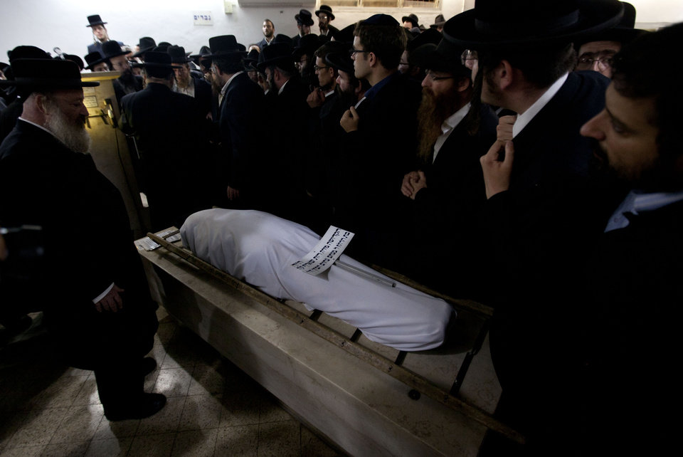 Photo -   Ultra Orthodox Jewish men gather around the body of Mirah Sharf who was killed in the southern town of Kiryat Malachi by a rocket thought to have been fired by Palestinian militants from the Gaza Strip, during her funeral in Jerusalem, Thursday, Nov. 15, 2012. Gaza militants led by the ruling Hamas Islamic group showered Israel with rockets in an unprecedented assault Thursday, killing three Israelis and trying for the first time to strike Tel Aviv, the densely populated heart of the Jewish state. (AP Photo/Sebastian Scheiner)