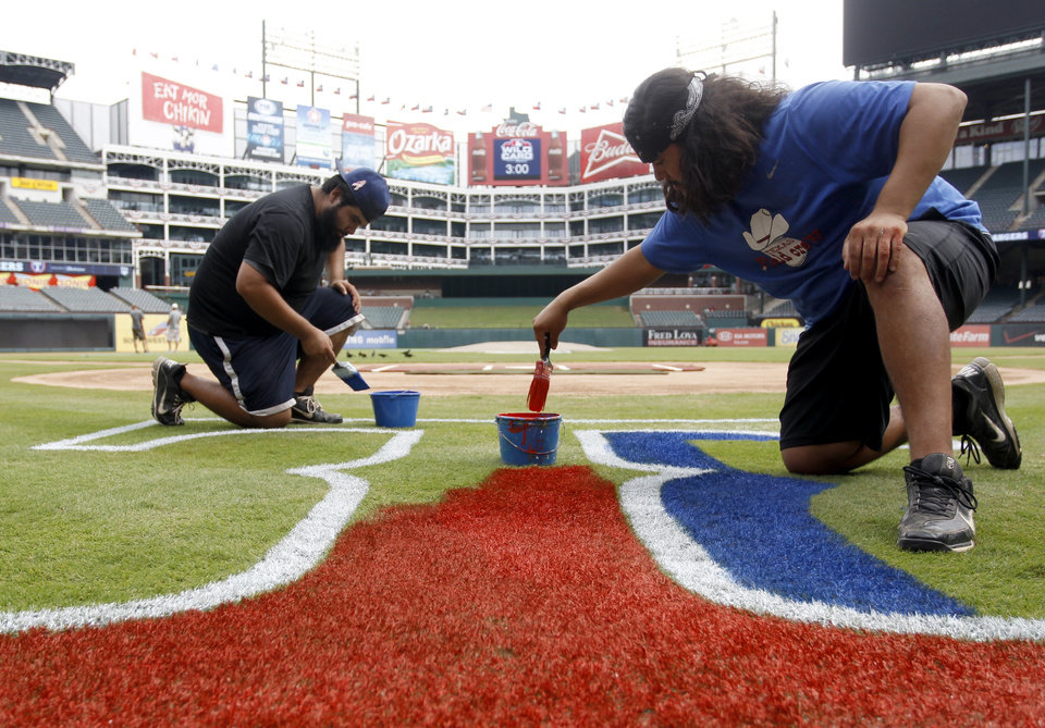 "From left, Mario Vargas and Jovan Vargas of the Texas Rangers Field Crew paint the letter ""T"" logo on the field in preparation of Friday's Wild Card game against the Baltimore Orioles at the Rangers Ballpark in Arlington, Texas on Thursday, Oct. 4, 2012. (AP Photo Richard W. Rodriguez)"