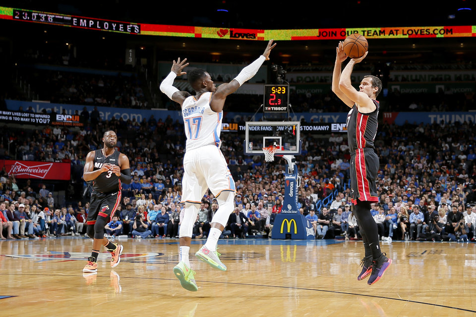 Photo - Miami's Goran Dragic (7) shoots a 3-pointer over Oklahoma City's Dennis Schroder (17) as Dwyane Wade (3) watches during an NBA basketball game between the Oklahoma City Thunder and the Miami Heat at Chesapeake Energy Arena in Oklahoma City, Monday, March 18, 2019. Miami won 116-107. Photo by Bryan Terry, The Oklahoman
