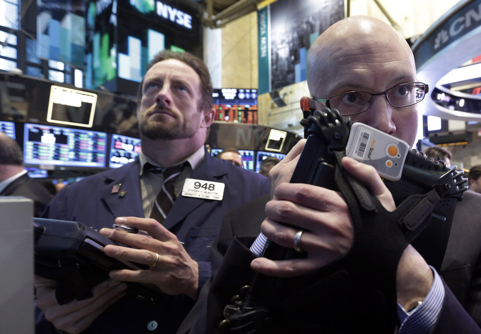 Photo - Traders Stephen Gilmartin, left, and Robert Armstrong work on the floor of the New York Stock Exchange Wednesday, April 10, 2013. Stocks are opening higher on Wall Street, a day after the Dow Jones industrial average closed at its second all-time high in a week. (AP Photo/Richard Drew)