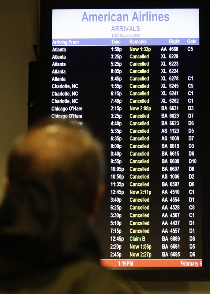 A patron checks to see if his flight is cancelled at LaGuardia Airport Friday, Feb. 8, 2013, in New York. Most airlines were giving up on flying in and out of New York, Boston and other airports in the American Northeast on Friday as a massive storm threatened to dump up to a meter of snow in some parts.  (AP Photo/Frank Franklin II) ORG XMIT: NYFF104