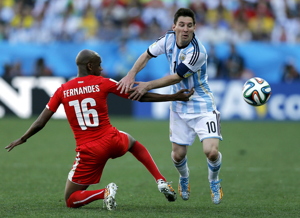 Photo - CORRECTS NAME OF MARCOS ROJO TO GELSON FERNANDES - Switzerland's Gelson Fernandes, left, tries to stop Argentina's Lionel Messi during the World Cup round of 16 soccer match between Argentina and Switzerland at the Itaquerao Stadium in Sao Paulo, Brazil, Tuesday, July 1, 2014. (AP Photo/Victor R. Caivano)