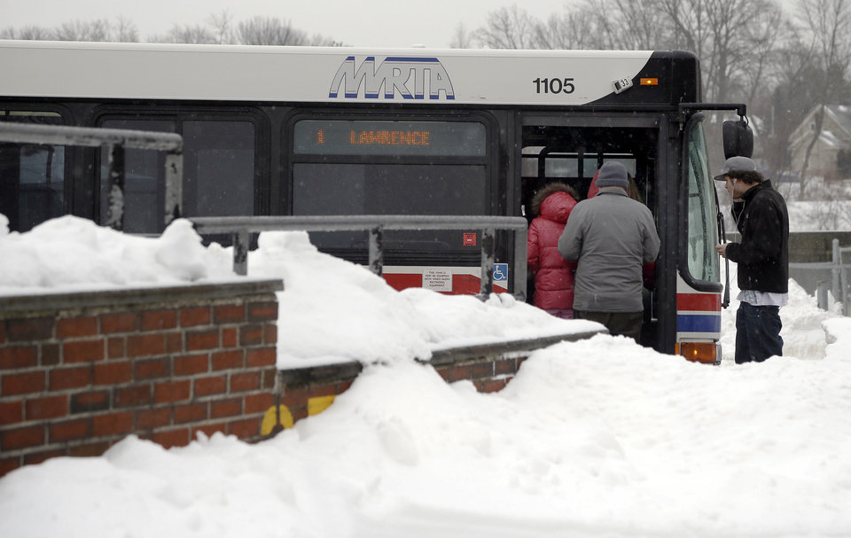 Travelers board a bus at the MRTA station in Haverhill, Mass. Monday, Feb. 11, 2013. State officials urged commuters to take public transportation when possible. The MBTA's regularly scheduled service resumed Monday, but some trolley and commuter rail lines were experiencing delays due to signal problems and weather-related issues. (AP Photo/Elise Amendola)