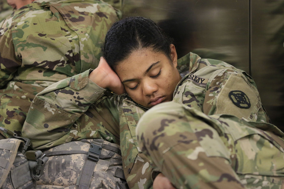 Photo - Lyka Johnson tries to get a little sleep before her flight to San Diego, CA, as soldiers from Ft. Sill gather at Will Rogers World Airport in Oklahoma City, Okla. on their way home for Christmas, Monday, Dec. 19, 2016.  Photo by Paul Hellstern, The Oklahoman