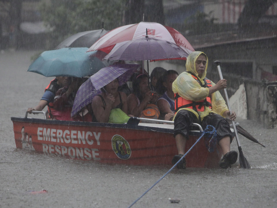A man uses a boat Wednesday to carry people across a flooded street in San Juan, east of Manila, Philippines. Widespread flooding that paralyzed the Philippine capital began to ease Wednesday as rescue efforts focused on a large number of distressed residents, some still marooned on their roofs. AP Photo
