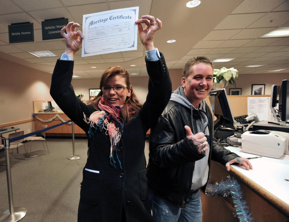 Photo - Sarah, left, and Melissa Adams show off the first same-sex marriage license approved at the Whatcom County Auditor's Office at the Whatcom County Courthouse in Bellingham, Wash., on Thursday, Dec. 6, 2012, on the first day the state's law legalizing gay marriage goes into effect.(AP Photo/The Bellingham Herald, Philip A. Dwyer)