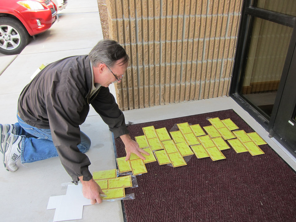 """Photo -  Victor  Hochla, a parishioner at St. Andrew Catholic Church, places bricks forming a """"Wizard of Oz""""-themed yellow pathway from one building to another at the church complex at 805 NW 5 in Moore. Photo by Carla Hinton, The Oklahoman"""