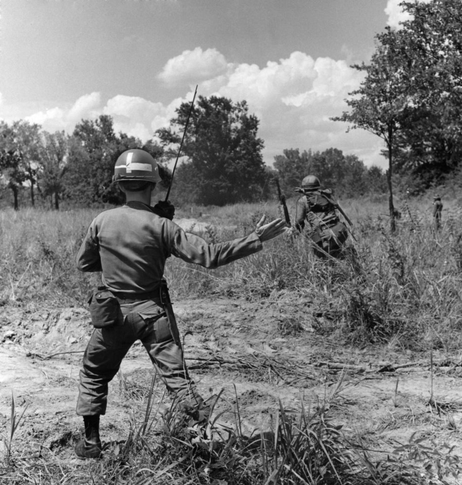 Photo -  A Kingfisher lieutenant leads his Thunderbirds through a live-fire platoon attack at Fort Chaffee.  Staff photo by George Tapscott.  Photo dated 08/08/1963 and published on 08/10/1963 in The Daily Oklahoman.