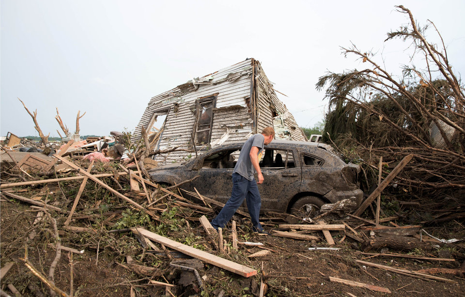 Photo - Tim Nelson  searches for survivors in Pilger, Neb.,  after the town was hit by a tornado Monday June 16, 2014.  Ast least one person has died due to the storm.  (AP Photo/The Omaha World-Herald/Ryan Soderlin)  MAGS OUT; ALL NEBRASKA LOCAL BROADCAST TV OUT