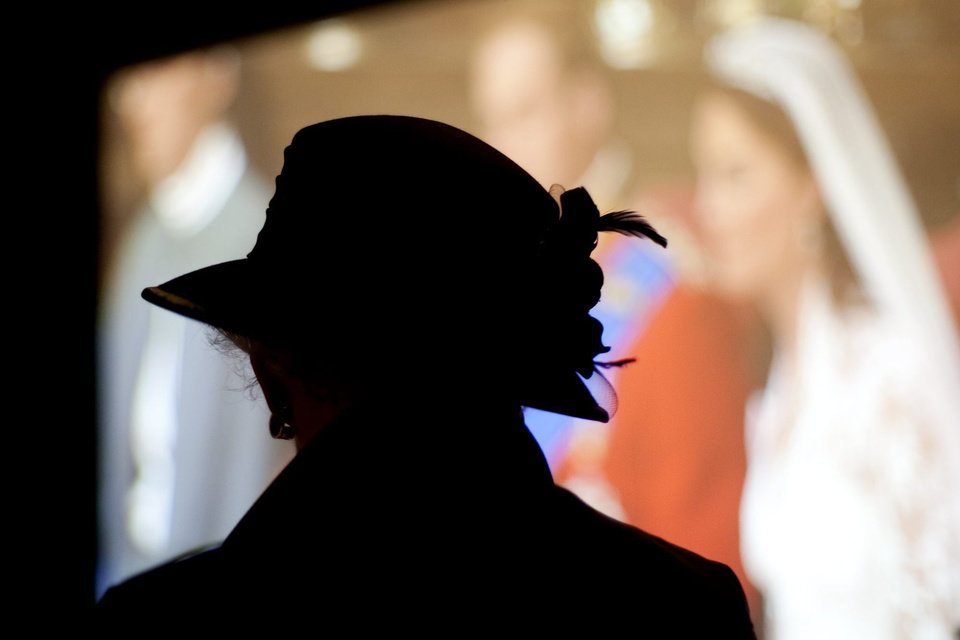 Photo - A woman is silhouetted while watching the royal wedding between Prince William and Kate Middleton on a large television screen at the King Edward hotel in Toronto Friday, April 29, 2011. (AP Photo/The Canadian Press, Darren Calabrese) ORG XMIT: DBC104