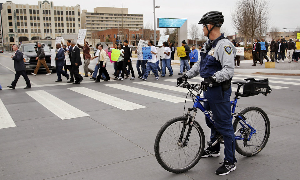 Photo - An Oklahoma City police officer blocks traffic on N Walker so the Rev. Jackson and protesters can cross the street on their way to City Hall. Photo by Jim Beckel, The Oklahoman  Jim Beckel