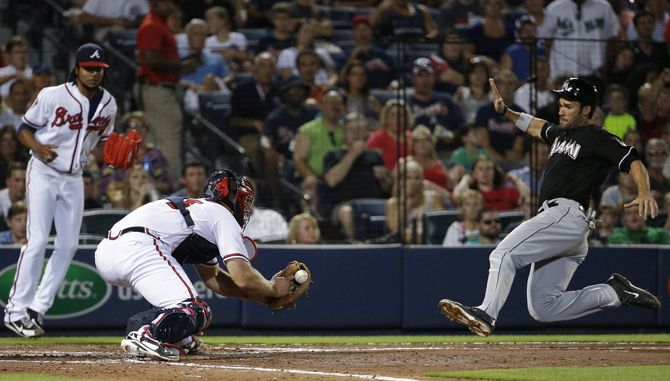 Photo - Atlanta Braves catcher Evan Gattis, center, waits with the ball to tag out Miami Marlins' Garrett Jones, right, as he tries to score off a single by teammate Marcell Ozuna as Atlanta Braves pitcher Ervin Santana, left, looks on in the sixth inning of a baseball game, Friday, Aug. 29, 2014, in Atlanta. (AP Photo/David Goldman)