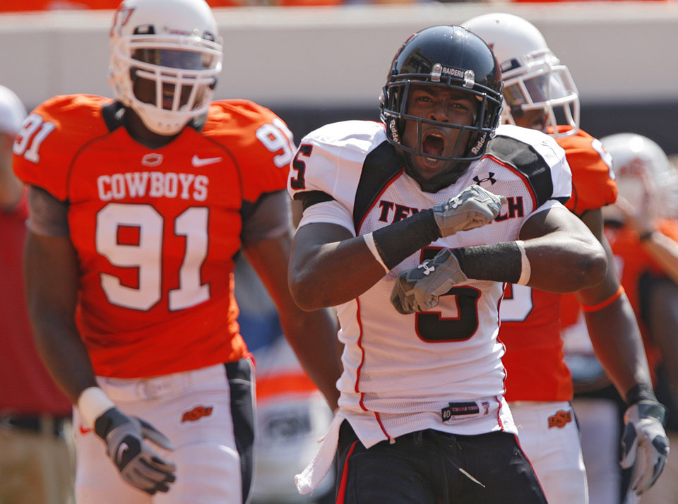 Photo - Texas Tech's Michael Crabtree (5) celebrates after a touchdown in front of Oklahoma State's Ugo Chinasa (91) during the first half of the college football game between the Oklahoma State University Cowboys (OSU) and the Texas Tech University Red Raiders (TTU) at Boone Pickens Stadium  on Saturday, Sept. 22, 2007, in Stillwater, Okla. 