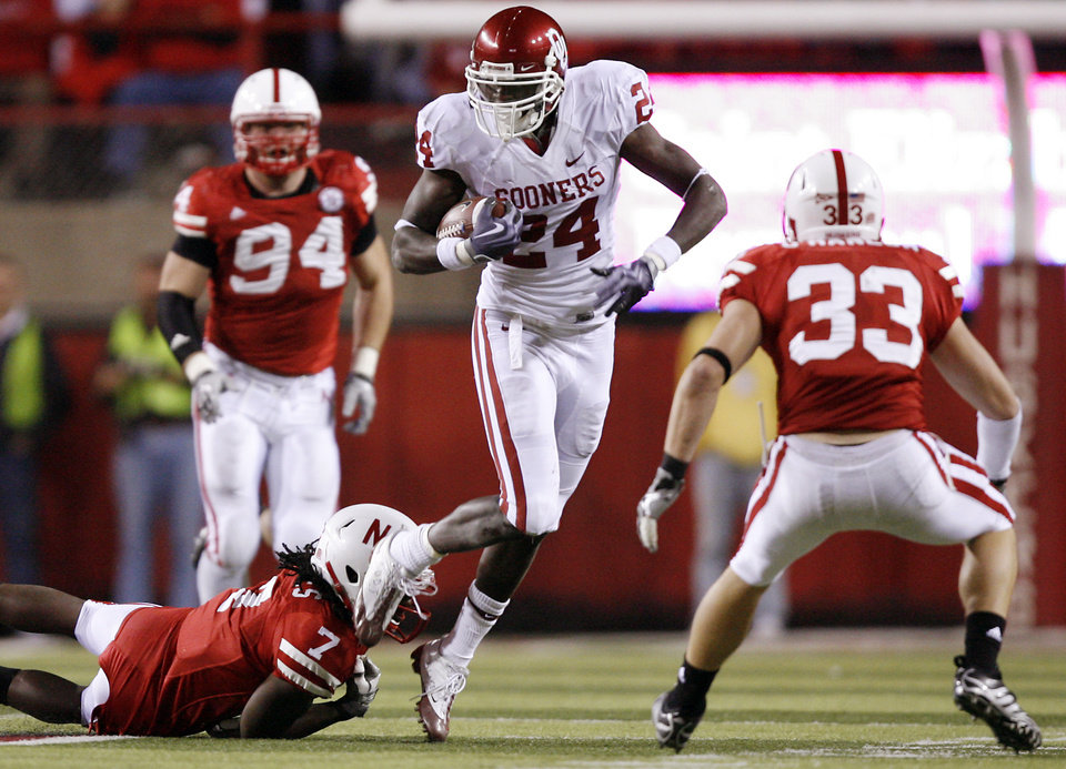 Photo - Oklahoma's Dejuan Miller (24) goes for extra yards against Nebraska's Dejon Gomes (7) and Matt O'Hanlon (33) during the second half of the college football game between the University of Oklahoma Sooners (OU) and the University of Nebraska Cornhuskers (NU) on Saturday, Nov. 7, 2009, in Lincoln, Neb.