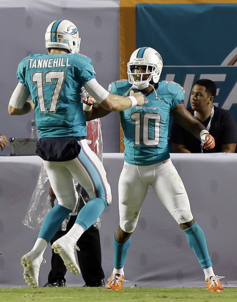 Photo - Miami Dolphins wide receiver Brandon Gibson (10) celebrates a touchdown with quarterback Ryan Tannehill (17) during the first half of a preseason NFL football game against the Tampa Bay Buccaneers, Saturday, Aug. 24, 2013, in Miami Gardens, Fla. (AP Photo/Wilfredo Lee)