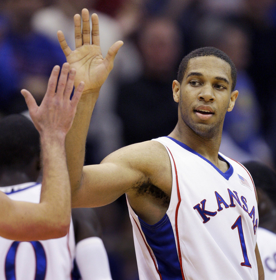 Photo - University of Kansas guard Xavier Henry (1) is congratulated by a teammate during the first half of an NCAA college basketball game against Radford Wednesday, Dec. 9, 2009, in Lawrence, Kan. Henry scored 13 points to help Kansas defeat Radford 99-64. (AP Photo/Orlin Wagner) ORG XMIT: KSOW107