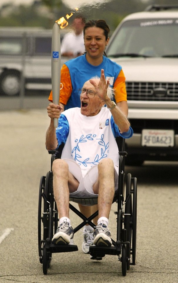 Photo - FILE - In a June 16, 2004 file photo, Louis Zamperini, 86, reacts to cheers from the crowd as he rides through the Dodger Stadium parking lot during the Olympic Torch Relay, in Los Angeles. Zamperini, a U.S. Olympic distance runner and World War II veteran who survived 47 days on a raft in the Pacific after his bomber crashed, then endured two years in Japanese prison camps, died Wednesday, July 2, 2014, according to Universal Pictures studio spokesman Michael Moses. He was 97. (AP Photo/Mark J. Terrill, File)
