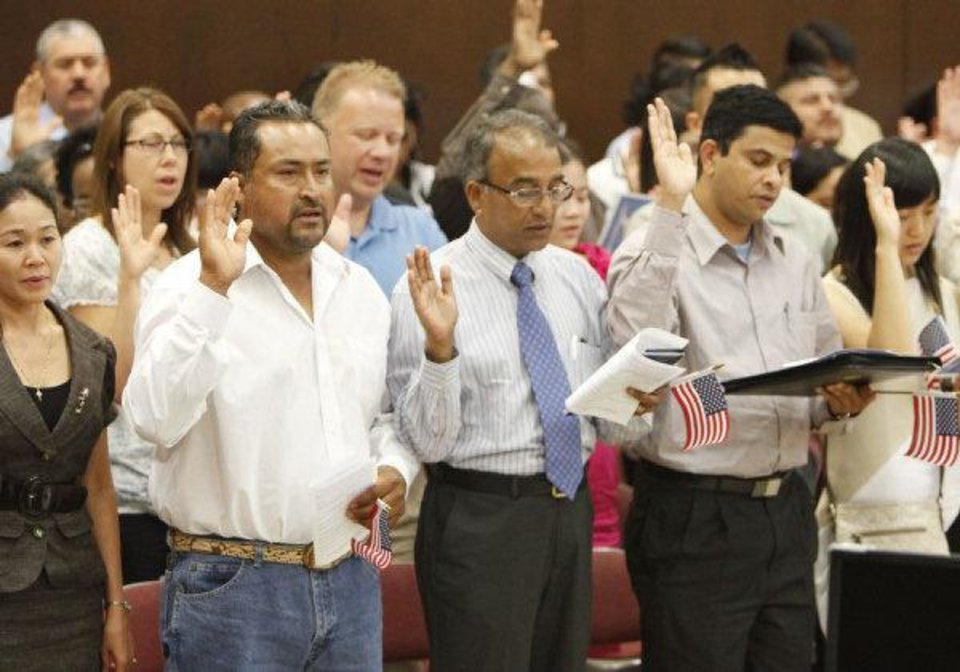 Photo - Former Mexican citizen Ernesto Rosas (left) and former Indian citizens Simon Mascarenhas and George Varghese take the oath of citizenship during a June 24 naturalization ceremony at the federal courthouse in Oklahoma City.  PAUL HELLSTERN - THE OKLAHOMAN