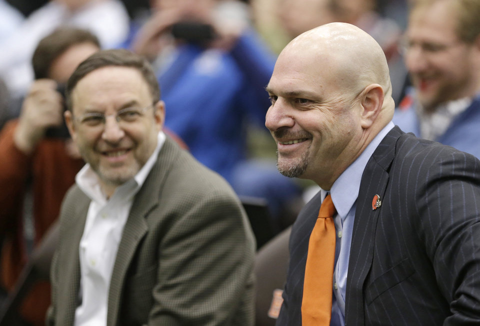 Photo - Cleveland Browns coach Mike Pettine, right, smiles as he sits next to the NFL football team's CEO, Joe Banner, left, before Pettine was introduced to the media Thursday, Jan. 23, 2014, in Berea, Ohio. Pettine inherits a Cleveland team that went 4-12 this season after losing its last seven games. (AP Photo/Tony Dejak)