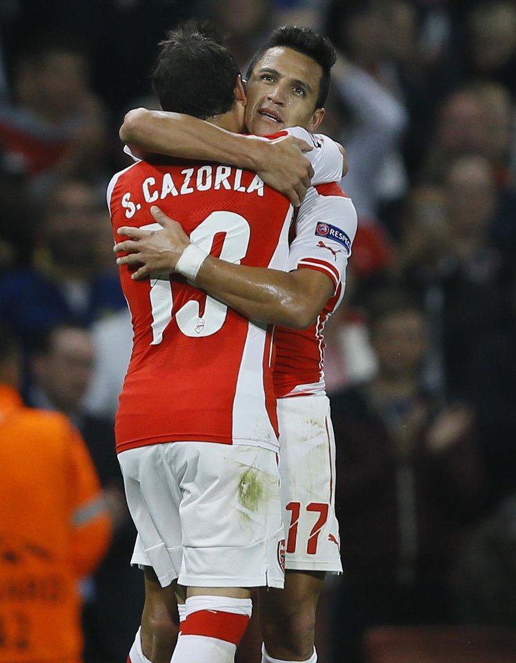 Photo - Arsenal's Alexis Sanchez, right, celebrates with teammate Santi Cazorla after scoring a goal during a second leg Champions League qualifying soccer match between Arsenal and Besiktas at Emirates Stadium in London Wednesday, Aug. 27, 2014.(AP Photo/Kirsty Wigglesworth)