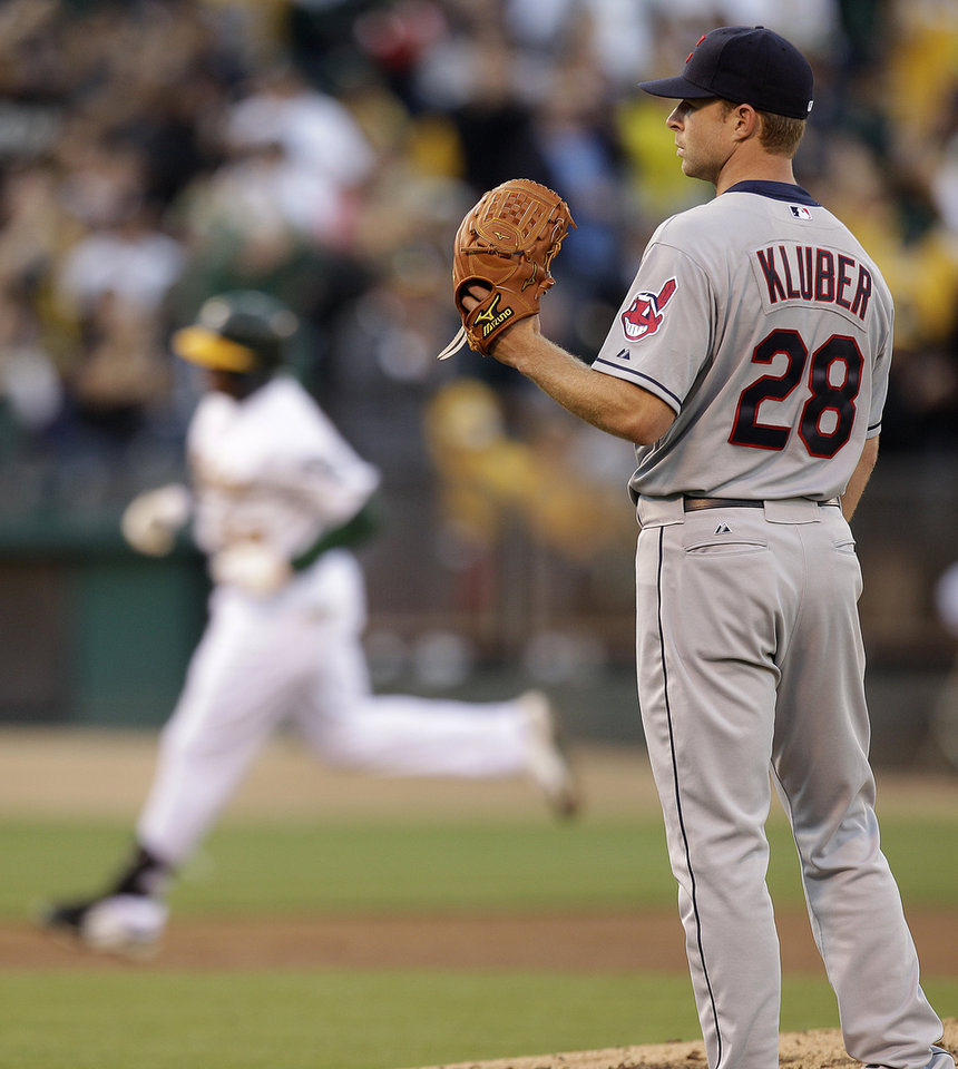 Cleveland Indians' Corey Kluber, right, waits for Oakland Athletics' Yoenis Cespedes to run the bases on a two-run home run in the third inning of a baseball game Saturday, Aug. 18, 2012, in Oakland, Calif. (AP Photo/Ben Margot)
