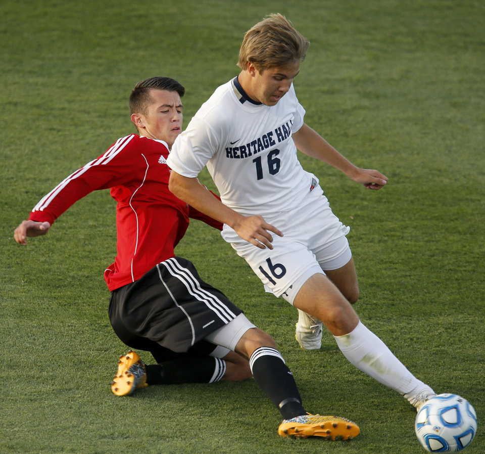 Photo - Heritage Hall's Matt McLaughlin goes past Skiatook's Maverick Hunt during the Class 5A boys soccer championship between Heritage Hall and Skiatook in Norman, Okla., Friday, May 16, 2014. Photo by Bryan Terry, The Oklahoman