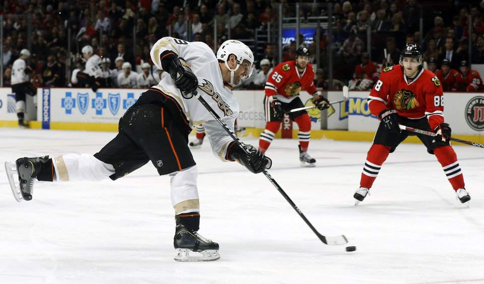 Anaheim Ducks defenseman Francois Beauchemin shoots on goal as Chicago Blackhawks right wing Patrick Kane (88) watches during the first period of an NHL hockey game, Tuesday, Feb. 12, 2013, in Chicago. (AP Photo/Charlie Arbogast)