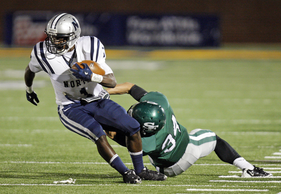 Edmond North\'s Jarion Tudman (1) tries to break away from Conner Bays (34) of Edmond Santa Fe during a high school football game between Edmond Santa Fe and Edmond North at Wantland Stadium in Edmond, Okla., Friday, Oct. 28, 2011. Photo by Nate Billings, The Oklahoman