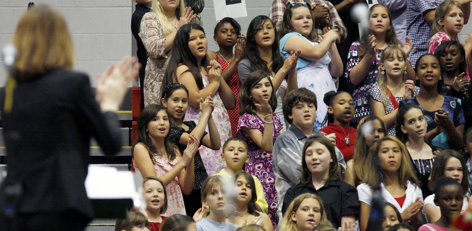 Photo - Over 700 fourth and fifth grade students from the Mid-Del school district, conducted by Suzanne Morrison, perform during the 57th Annual Elementary Vocal Music Festival at the Carl Albert High School Fieldhouse in Midwest City, Okla. on Thursday, April 30, 2009. BY BRENDA O'BRIAN, THE OKLAHOMAN