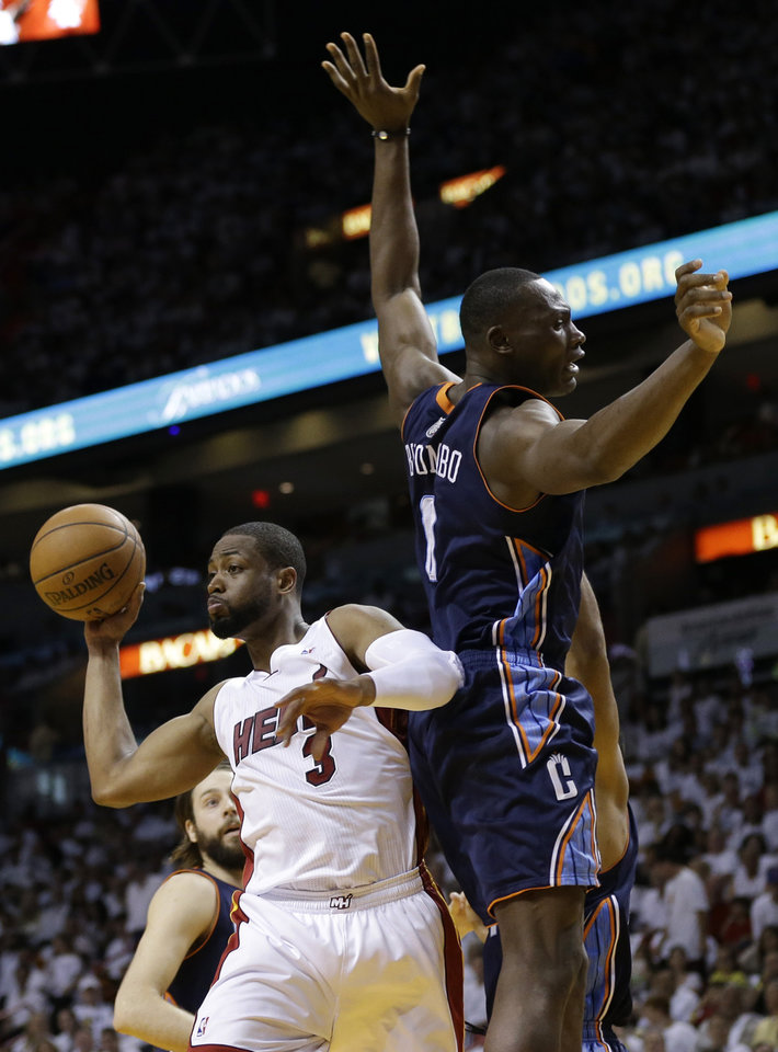 Photo - Miami Heat's Dwyane Wade (3) passes the ball as Charlotte Bobcats' Bismack Biyombo (0) defends during the first half in Game 1 of an opening-round NBA basketball playoff series, Sunday, April 20, 2014, in Miami. (AP Photo/Lynne Sladky)