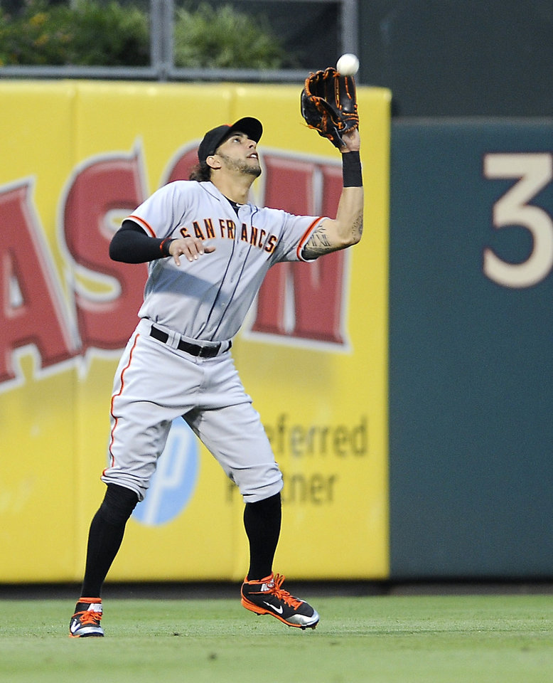 Photo - San Francisco Giants left fielder Michael Morse catches a fly ball hit by Philadelphia Phillies' Jimmy Rollins in the third inning of a baseball game on Tuesday, July 22, 2014, in Philadelphia. (AP Photo/Michael Perez)