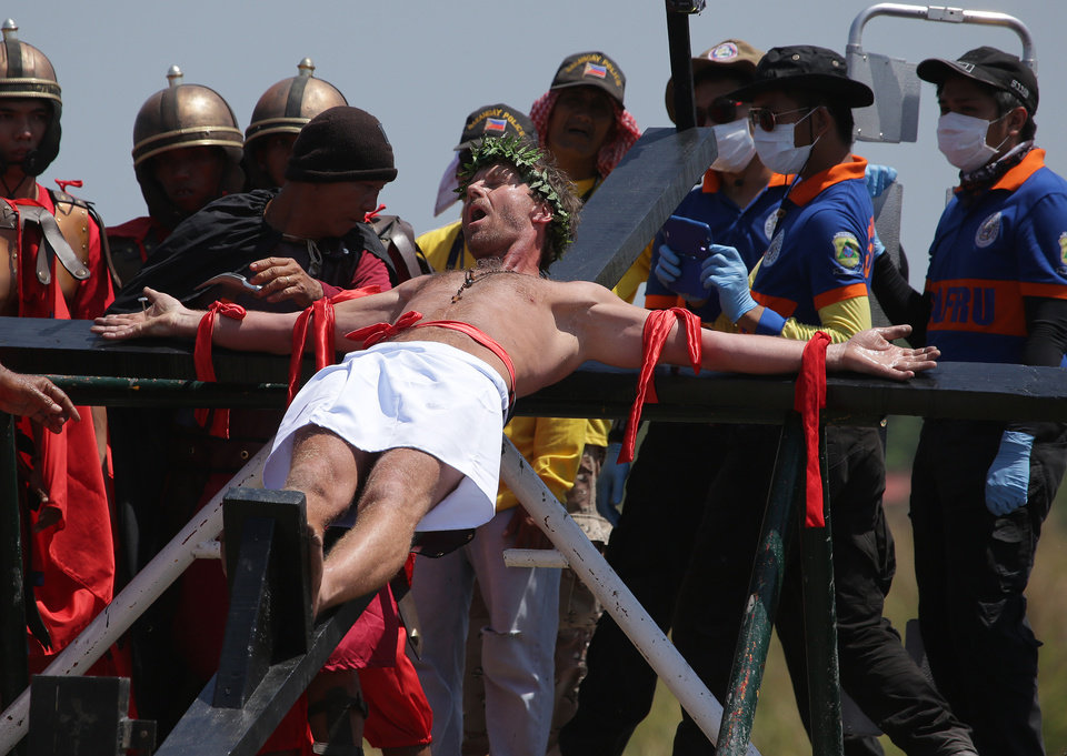 Photo - CORRECTS NAME OF THE VILLAGE - Danish national Lasse Spang Olsen, a 48-year-old filmmaker, grimaces as he is nailed to a cross to re-enact the crucifixion of Jesus Christ in San Pedro Cutud village, Pampanga province, northern Philippines on Friday, April 18, 2014. Church leaders and health officials have spoken against the practice which mixes Roman Catholic devotion with folk belief, but the annual rites continue to draw participants and huge crowds. (AP Photo/Aaron Favila)