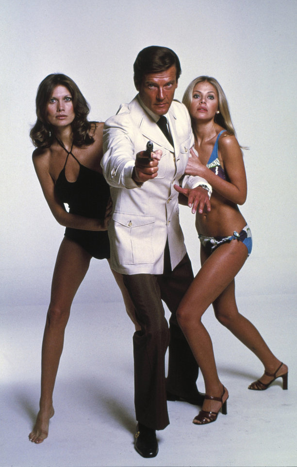 This undated publicity photo provided by United Artists and Danjaq, LLC shows Roger Moore, center, with Maud Adams, left, and Britt Ekland, from the James Bond 1974 film,