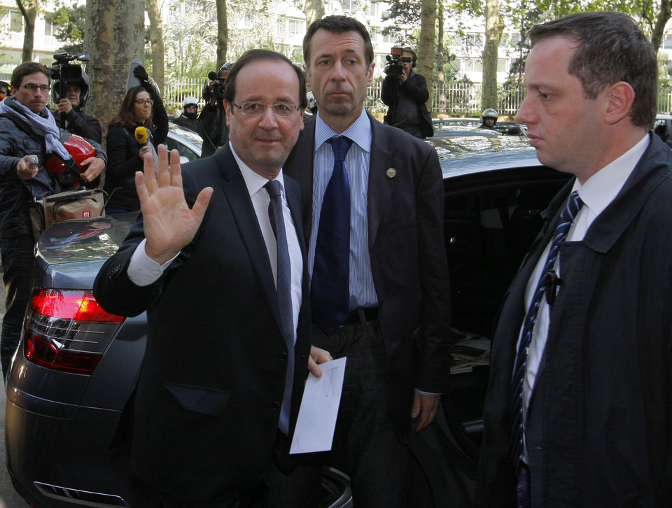 Photo -   President-elect Francois Hollande, left, waves as he arrives at the Socialist Party headquarters in Paris Monday May 7, 2012. France handed the presidency to leftist Hollande, a champion of government stimulus programs who says the state should protect the downtrodden, a victory that could deal a death blow to the drive for austerity that has been the hallmark of Europe in recent years. (AP Photo/Michel Spingler)