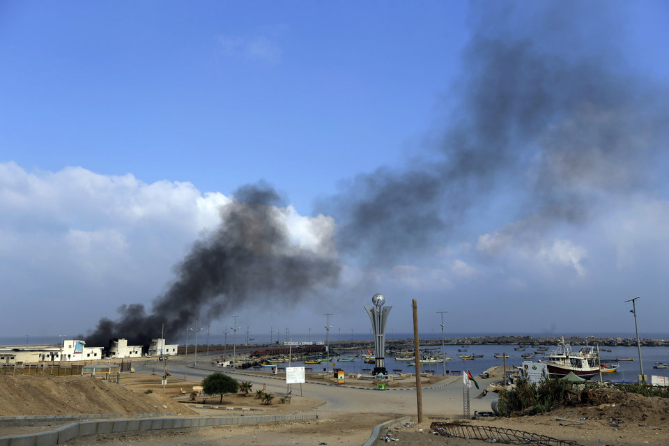 Photo - Smoke rises at the port in Gaza City, northern Gaza Strip, hit by an Israeli strike, Tuesday, July 29, 2014. According to Palestinians, the storage area at the port where the fishermen keep their nets and equipment was hit. Early Tuesday, Israel warplanes struck a series of targets in Gaza City, including Hamas leader Ismael Haniyeh's house and government offices, while Gaza's border area with Israel was hit by heavy tank shelling. (AP Photo/Lefteris Pitarakis)