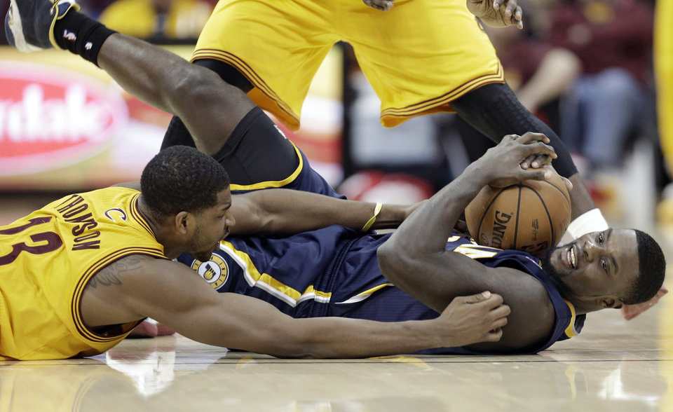 Photo - Cleveland Cavaliers' Tristan Thompson, left, and Indiana Pacers' Lance Stephenson battle for a loose ball in the second quarter of an NBA basketball game Sunday, Jan. 5, 2014, in Cleveland. (AP Photo/Tony Dejak)