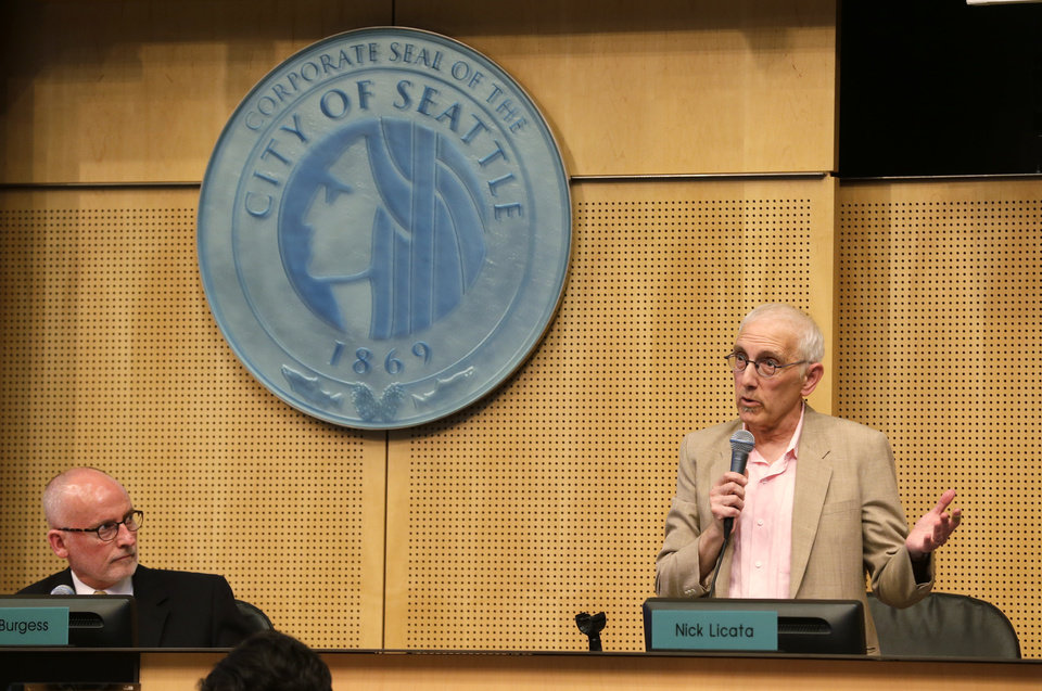 Photo - Seattle City Council member Nick Licata, right, speaks next to the seal of the City of Seattle as Council president Tim Burgess, left, looks on, Monday, June 2, 2014, during debate before the Council passed a$15 minimum wage measure. (AP Photo/Ted S. Warren)