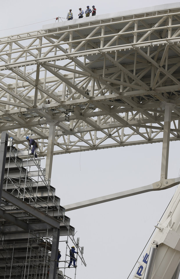 Photo - Laborers work on the construction of the Itaquerao stadium in Sao Paulo, Brazil, Tuesday, April 22, 2014. FIFA Secretary General Jerome Valcke said Tuesday there's still a lot of work to do at the stadium, but added that it will be ready for the opening match between Brazil and Croatia in June. (AP Photo/Andre Penner)